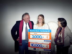 Ami Dose, Gründerin der Hamburger Tafel, und Hinz&Kunzt-Geschäftsführer  Jens Ade haben gut lachen: Sie teilen sich die Schecks über insgesamt 13.000 Euro Spenden der Aktion ObdacHHamburg und der Sparda-Bank