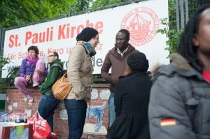 St. Paulianerin Georgie im Gespräch mit einem der afrikanischen Flüchtlinge. Die 29-Jährige war eine der ersten Helferinnen in der Kirche.