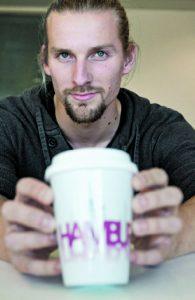 """Praktisch, schick und in Deutschland hergestellt: Azubi Max zeigt stolz den """"Hamburg zeigt Herz""""-Becher für unterwegs, der jetzt auch im Hinz&Kunzt-Shop zu kaufen ist."""