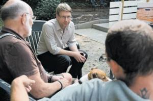 OLAF BOHN (Mitte) im Gespräch mit Gästen vor dem Hans-Fitze-Haus. Bei schönem Wetter ist der Garten ein beliebter Treffpunkt. Foto: Mauricio Bustamante