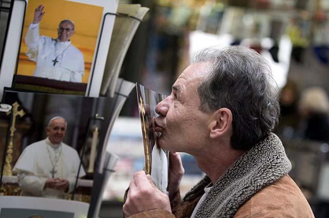 Ein Obdachloser küsst ein Foto von Papst Franziskus. Foto: Claudio Peri (picture alliance/dpa)
